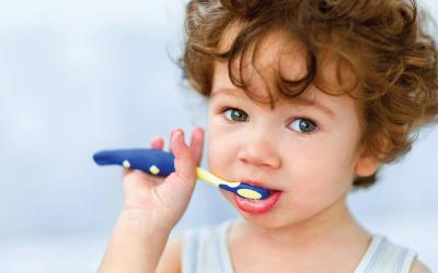 Young brown haired child brushing teeth