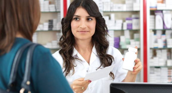 Pharmacist with long dark hair assisting customer in dark green shirt